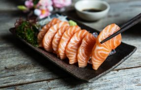 salmon-sashimi-japanese-food-with-soy-sauce-wooden-table_164138-287